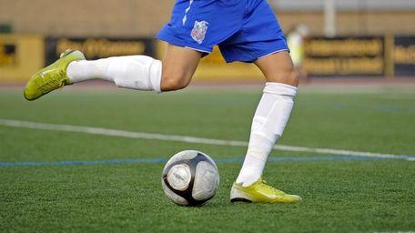A Rough Rider kicks the soccer ball in