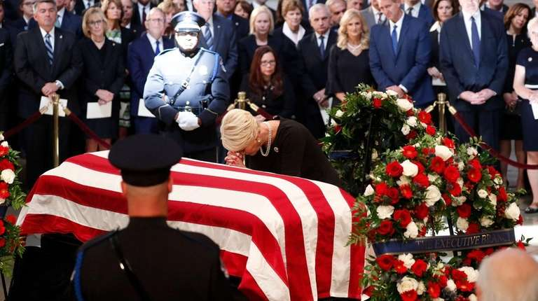Cindy McCain prays at the coffin of her