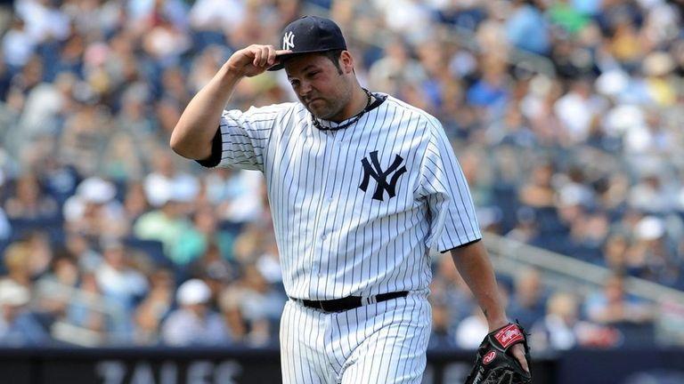 Yankees relief pitcher Joba Chamberlain walks back to