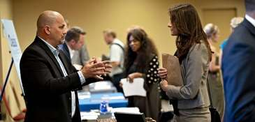 A company representative, left, speaks with a job