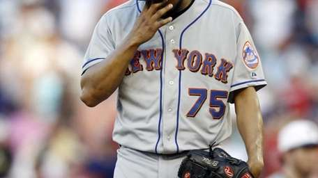 Mets reliever Francisco Rodriguez wipes his face after