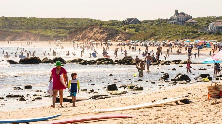 Beachgoers soak up the waning summer sun at