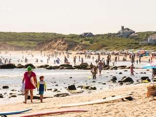Beachgoers soak up the waning summer sun at