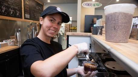 Angelina Perry prepares a frozen acai bowl at