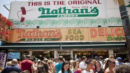 People crowd outside of the original Nathan's Famous