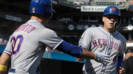 New York Mets' Wilmer Flores, right, is congratulated
