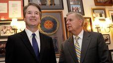 Supreme Court nominee Brett Kavanaugh stands with Sen.