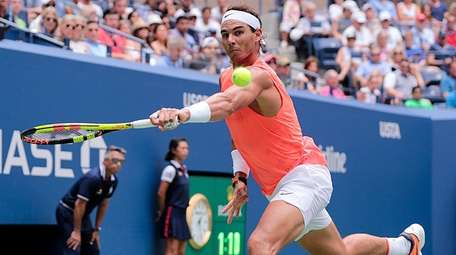 Rafael Nadal runs down a backhand return against