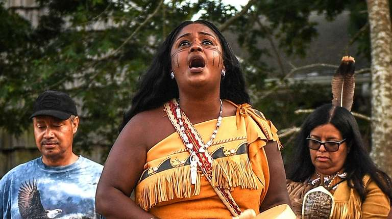 Shinnecock tribal member Chenae Bullock sings during a