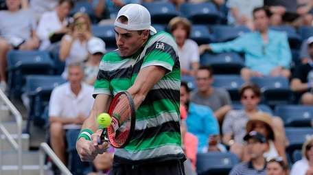 John Isner hits a backhand return during a