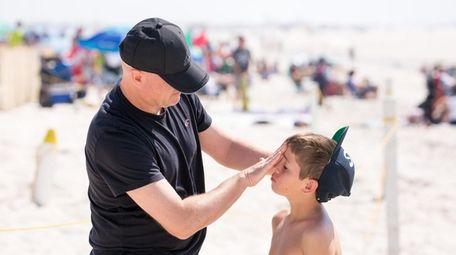 Bryan Faherty of Staten Island puts sunscreen on