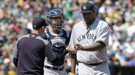 Yankees pitcher CC Sabathia, right, hands the ball