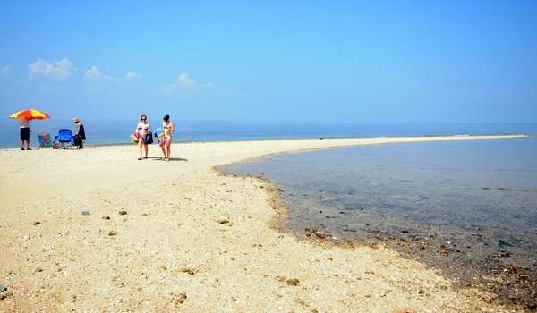 Beachgoers walk on a sandbar at Crab Meadow