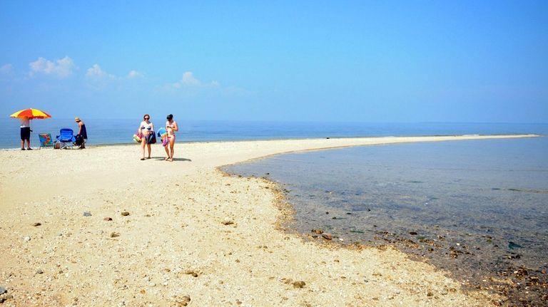 Beachgoers walk on a sandbar at Crab Meadow