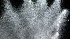 A sprinkler drenches a lawn on Long Island