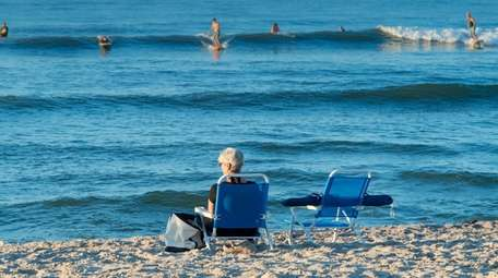 At sunrise Tuesday, Kathyrn Pirch, of Bohemia, watches