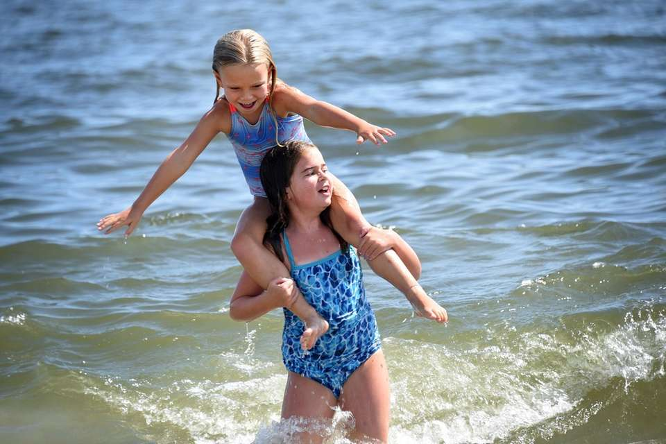 Maeve Emery, 6, sits atop the shoulders of