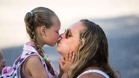 Ava Lafler, 5, kisses her mother, Meridith, as