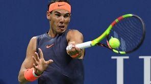 Rafael Nadal returns to Dominic Thiem during a