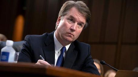Brett Kavanaugh takes notes as the Senate Judiciary