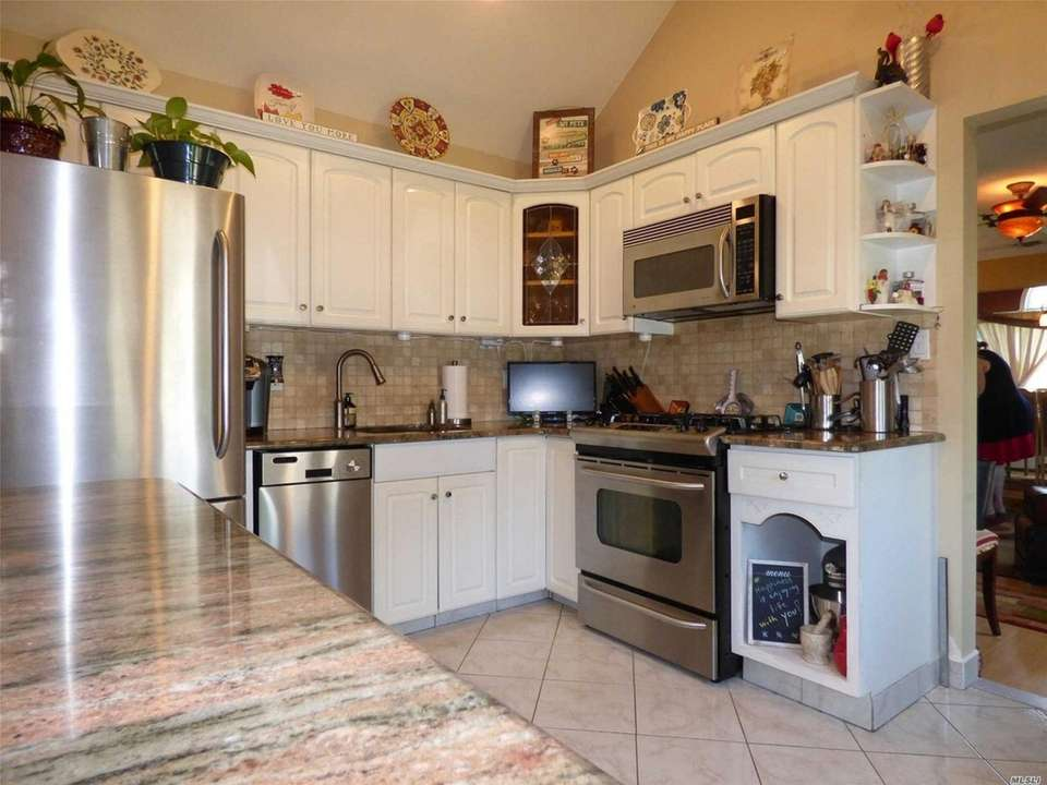 The granite kitchen features stainless steel appliances, a
