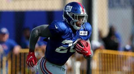 Saquon Barkley carries the ball during Giants training