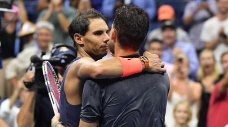 Rafael Nadal comes across the net to embrace