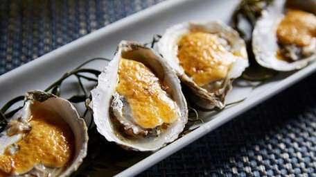 Grilled oysters accented with peppery Sriracha-sauce-spiked mayo highlight