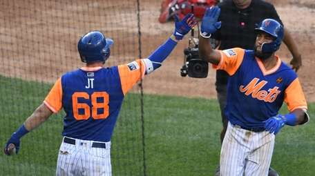 The Mets' Jeff McNeil, left, greets Amed Rosario