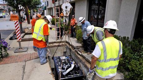A LIPA crew lowers a new transformer under