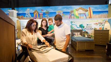 Saleswoman Maria Blandino, left, helps Christa and Tom