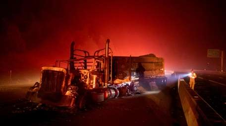 A scorched logging truck rests on Interstate 5