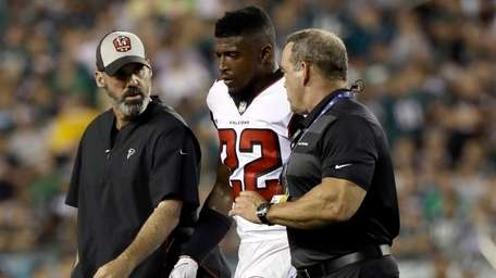 The Falcons' Keanu Neal is helped off the