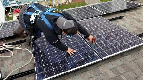Technician installs solar panels on the roof of