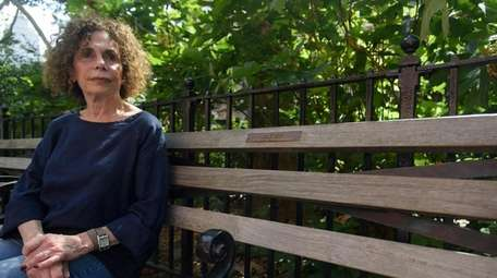 Phyllis Frank sits on a bench dedicated to