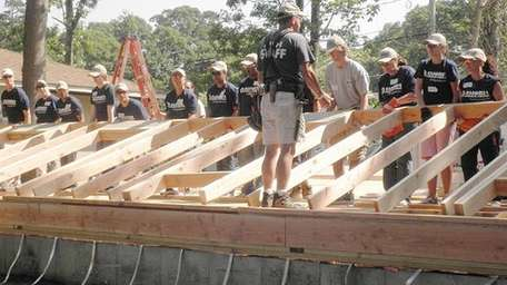 Bank workers raise a wall at a Habitat