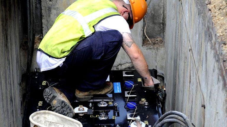 A LIPA technician installs a new transformer after