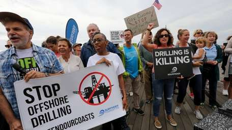 Demonstrators rally on the Long Beach boardwalk as