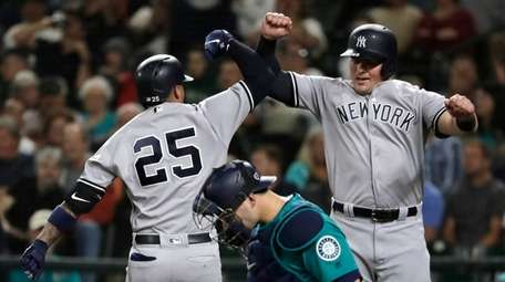 Yankees' Gleyber Torres, left, jumps to celebrate with
