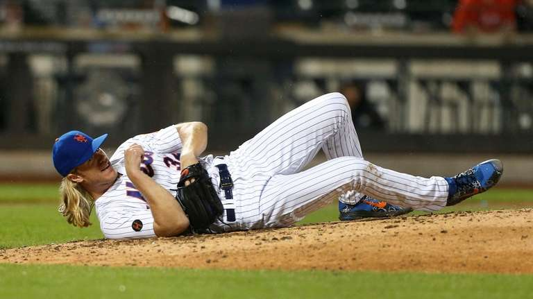 Noah Syndergaard lays on the mound after he