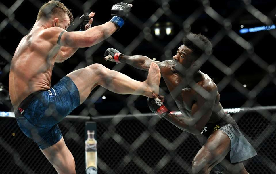 Aljamain Sterling, right, throws a punch as Cody