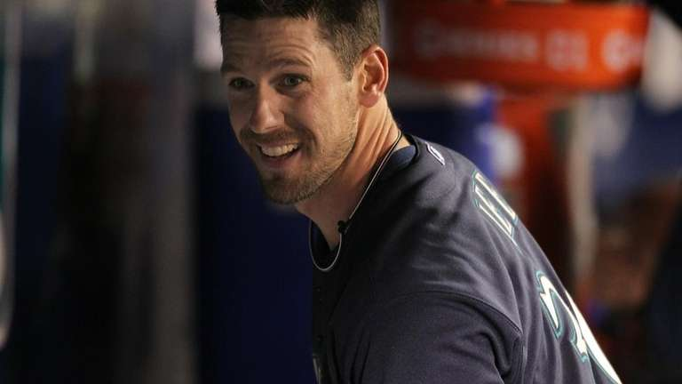 Starting pitcher Cliff Lee smiles in the dugout