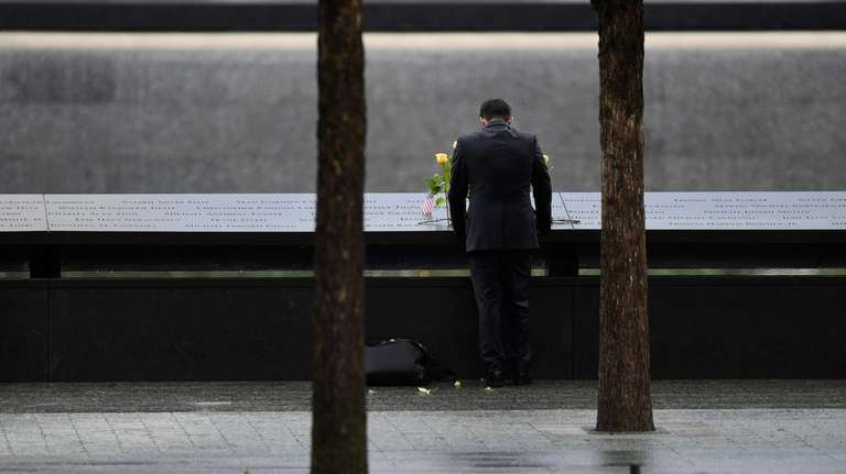 A person leaves flowers at the 9/11 memorial's