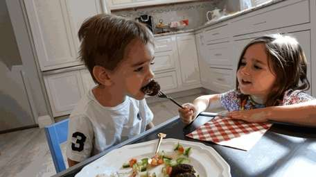 Maya Coppersmith, 4, feeds falafel to her brother