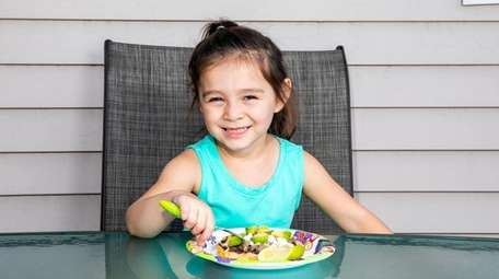 Naomi Romero, 4, with a plate of sopes