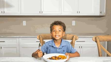 Troy Fernan, 5, with Oxtail, rice and peas