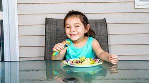 Naomi Romero, 4, digs into a plate of