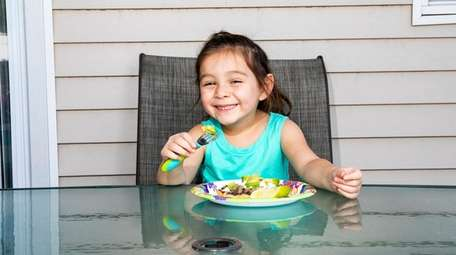 Naomi Romero, 4, digs into a plate of