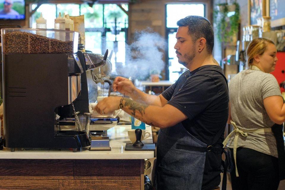 Barista Felix Torres brews espresso behind the bar