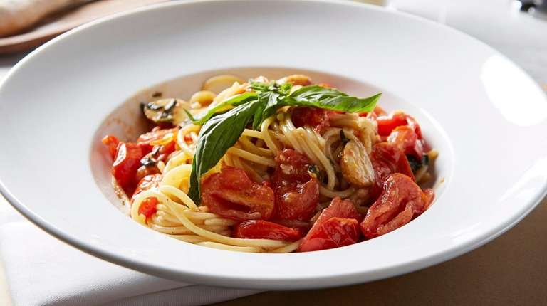 The signature dish, spaghetti al pomodorino, is tossed,